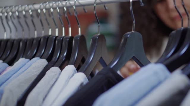 Shopper is moving hangers with tee shirts in sportive clothing store, close-up Young woman is viewing t-shirts on rack in trading area in store. Detail view of hangers and her hands, face is unfocused coathanger stock videos & royalty-free footage
