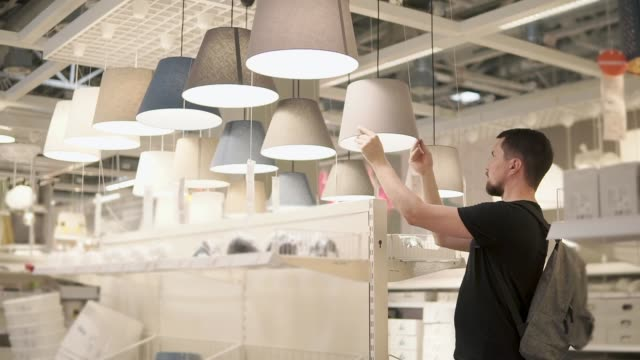 vídeos de stock, filmes e b-roll de homem do cliente está a examinar o sortimento de abajur em loja de varejo de grande - mobília