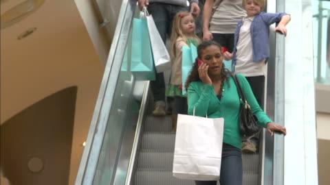shopper su scala mobile nel centro commerciale utilizzando il telefono cellulare - piano americano video stock e b–roll