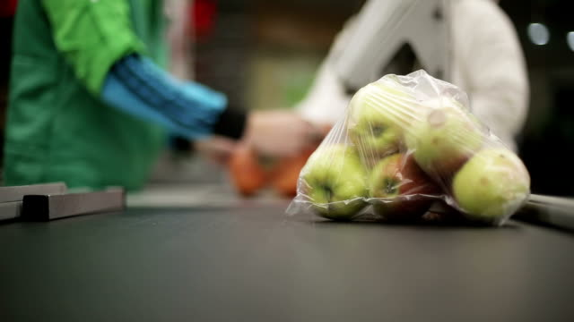 Shopper paying for products at checkout. Close up. Defocused video