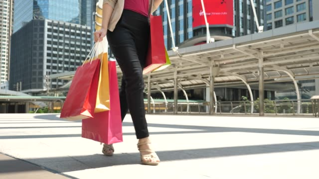 shopper walking with shopping bags in the city - borsa della spesa video stock e b–roll
