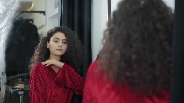 shopper kvinna klädd röd mode klänning njuter av hennes reflektion i spegeln - aftonklänning bildbanksvideor och videomaterial från bakom kulisserna