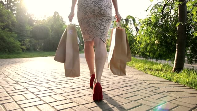 Shopper woman legs with shopping bags in street video