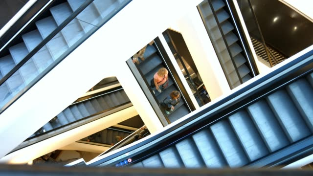 Shoppers Riding Crisscross Escalator in Shopping Mall video