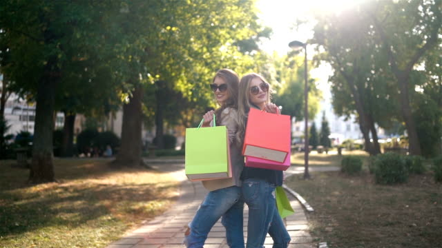 Shopping and walk in a park SLOW MOTION: Two beautiful women are posing with shopping bags in a park back to back stock videos & royalty-free footage