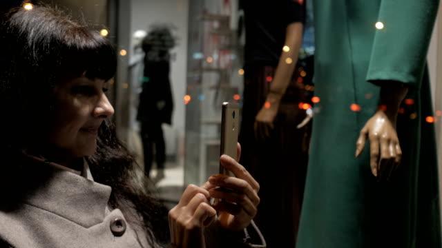 shopping på köpcentret, försäljning tid. kvinnan tittar på boutique showcase i kväll staden på gatan och tar ett foto. kvinna nära skyltfönstret med skyltdockor. läser streckkoder av smartphone. - köpnarkoman bildbanksvideor och videomaterial från bakom kulisserna