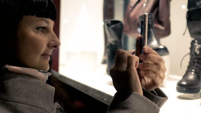 stockvideo's en b-roll-footage met winkelen bij winkelcentrum, verkooptijd. vrouw kijken naar boutique showcase in de avond stad op straat en neemt een foto. vrouw in de buurt etalage met mannequins. het lezen van streepjescodes door smartphone. zwarte vrijdag. - black friday shop