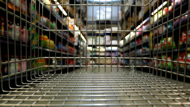 Shopping cart rush throung supermarket aisles Time lapse of empty shopping cart moving through supermarket. market retail space stock videos & royalty-free footage