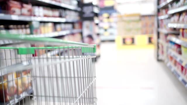 kundvagnen går långsamt framåt längs stormarknaden gång med suddig bakgrund, nytt normalt liv, fylla på mat, shoppingvaror leverans, slow motion, starkt vitt ljus. - dagligvaruhandel, hylla, bakgrund, blurred bildbanksvideor och videomaterial från bakom kulisserna