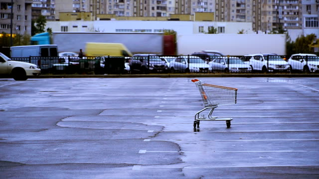 A shopping cart. The shopping trolley is in the parking lot A shopping cart. The shopping trolley is in the parking lot market retail space stock videos & royalty-free footage