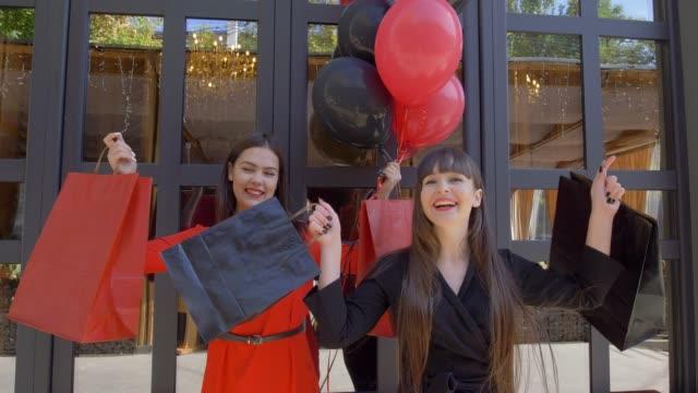 vídeos y material grabado en eventos de stock de compras día, felices amigas agitando bolsas con nuevas compras de tienda de moda en venta estacional en negro el viernes - black friday sale