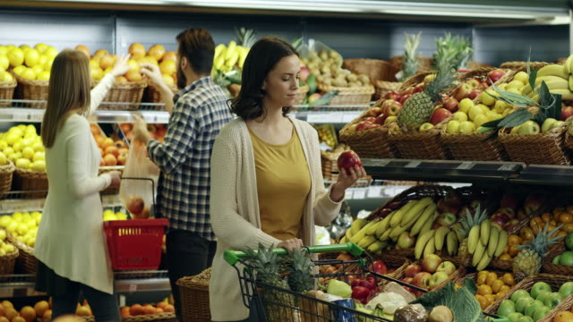 Shopping for groceries Young woman buying fruit at the Supermarket. shopping cart stock videos & royalty-free footage