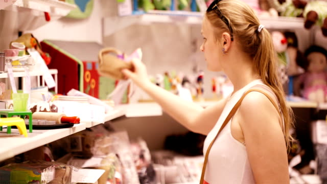 Shopping for toys in the supermarket Young woman is choosing toys for her kid in the toy's store in the supermarket toy stock videos & royalty-free footage