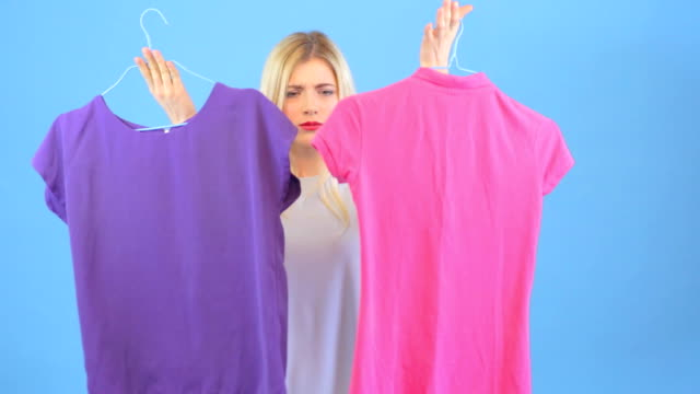 Shopping for t-shirts, young woman chooses clothes - vídeo