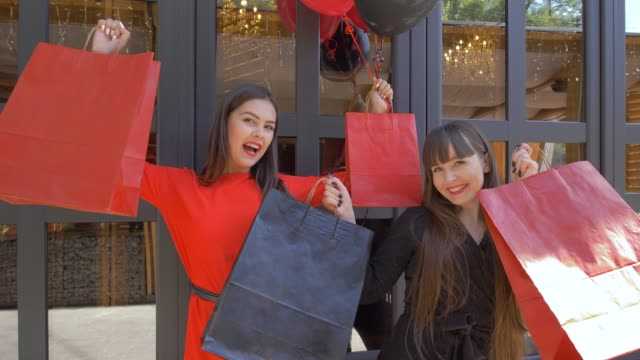 vídeos y material grabado en eventos de stock de de compras vacaciones, mujeres divertidas disfrutan de nuevas compras de tienda de caro en temporada de descuentos en black el viernes - black friday sale