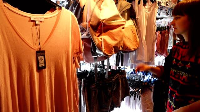vídeos y material grabado en eventos de stock de de compras en los puntos de europa. la chica elige ropa. - moda playera