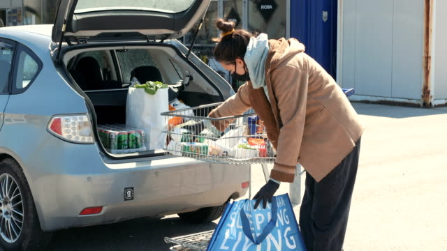 shopping is finished side view of young woman, she packing their groceries in her car car shopping stock videos & royalty-free footage