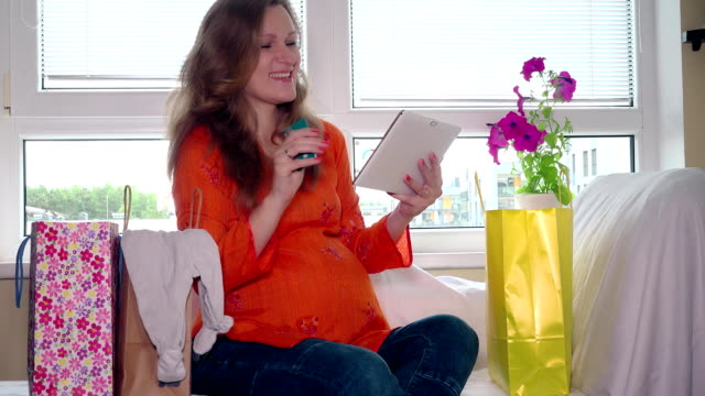 Shopping online in pregnancy time concept. Pregnant woman with tablet computer video