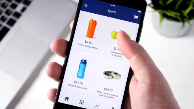 shopping online using smartphone app and choosing sport equipment - online shopping filmów i materiałów b-roll