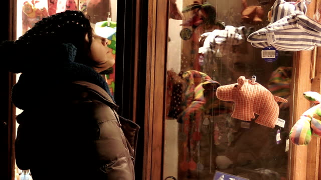 shopping time in the winter: woman in front of the window of a clothes shop video