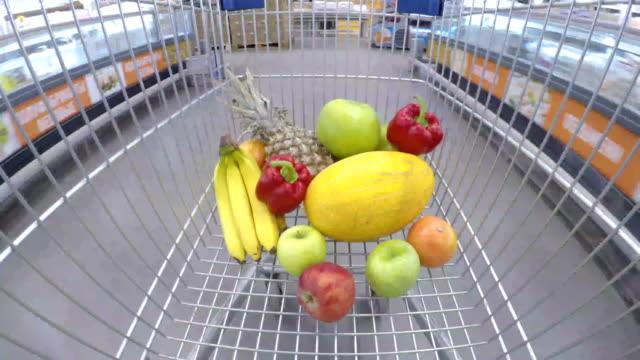 einkaufswagen mit frischem gemüse und obst durch supermarkt - bio lebensmittel stock-videos und b-roll-filmmaterial