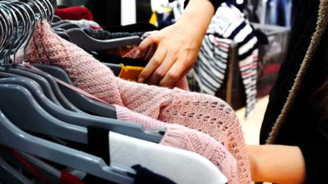 Shopping woman. Hands of shopper looking at clothes in clothes store. Close-up shot, handheld. video