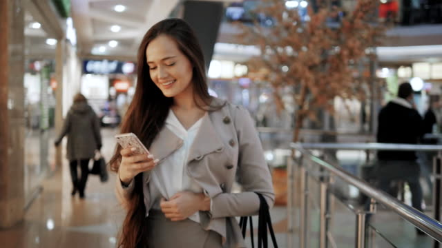Shopping woman smiling with bags talking on the phone in mall. Beautiful girl with smartphone in shopping center video