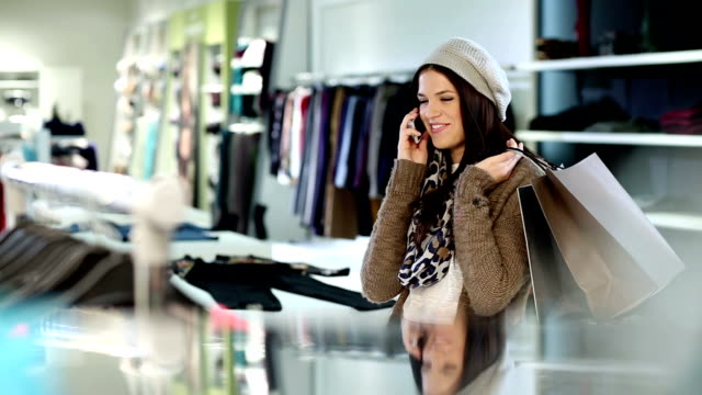 Shopping woman using mobile phone video
