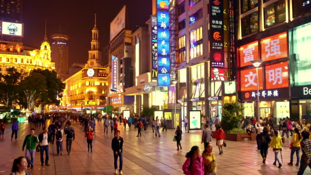 Shoppping Street in Shanghai, China Crowds walk below neon signs on Nanjing Road. The street is the main shopping district of the city and one of the world's busiest shopping districts. shanghai stock videos & royalty-free footage
