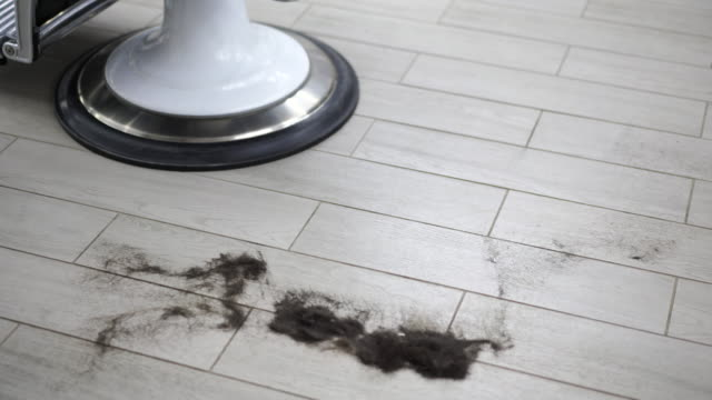 Short black male hair lies on the floor near barbershop armchair of the hairdresser after a haircut.