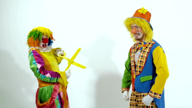 Short funny clown scares the other clown with huge scissors video