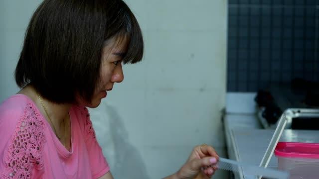 kurzhaarige asiatische frau schneiden ihre eigenen haare zu hause - indochina stock-videos und b-roll-filmmaterial