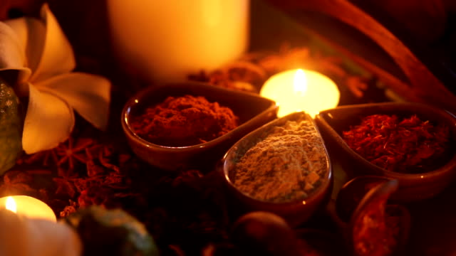 cu shot a set of herbal treatments for massage and spa decorated with frangipani and lighting candles. - alternative medicine stock videos and b-roll footage