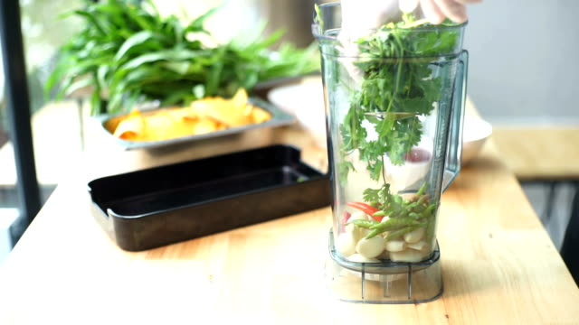 2 shot Dolly : Chef's pouring ingredients for makes Thai sauce in the blender, fresh coriander leaves, garlics, green and red chili on wooden table background. video