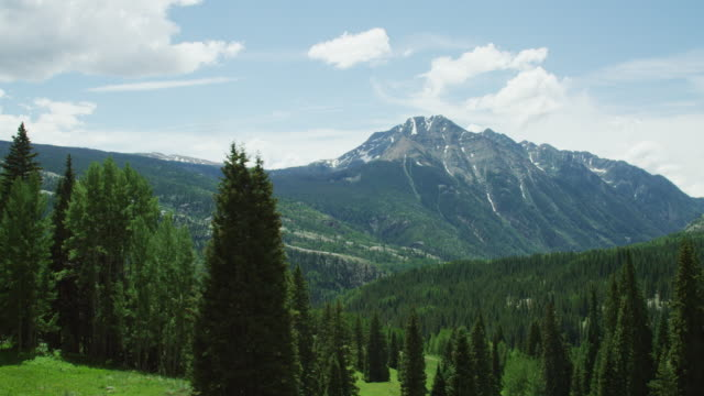shot from a moving vehicle of the san juan mountains in colorado as seen from red mountain pass (million dollar highway/us 550) through the rocky mountains in summer on a partly cloudy day - колорадо стоковые видео и кадры b-roll