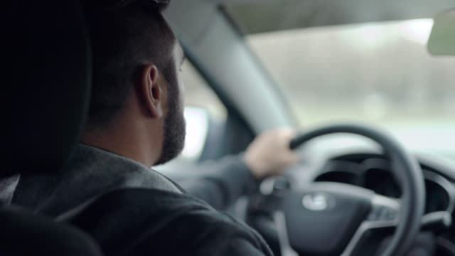 Shot from back seat of a car of a man driving in city Shot from back seat of a car of a man driving in city. Hands on steering wheel, urban driver. intercity stock videos & royalty-free footage