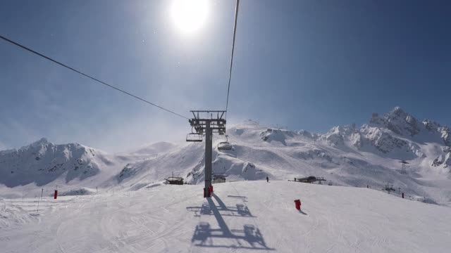 shot from the chair lift rises to the top of the mountain in winter ski resort - sci video stock e b–roll
