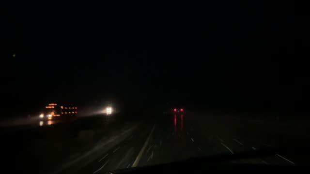夜の吹雪の間に交通渋滞で移動中の車両の前から撮影 - 州間高速道路点の映像素材/bロール