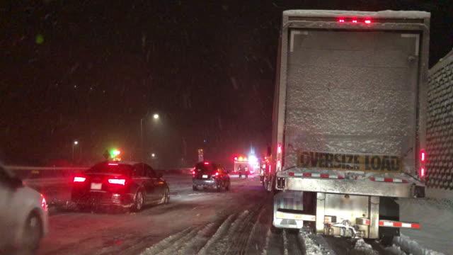 vidéos et rushes de tir de l'avant d'un véhicule tout en étant arrêté par un accident et les travailleurs d'urgence sur un interstate pendant une tempête de neige la nuit - blizzard
