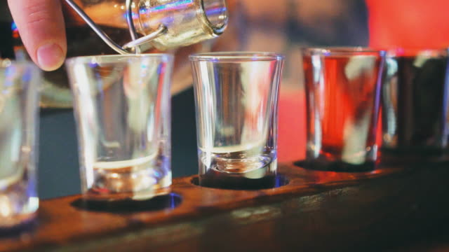Shot glasses with liquor in the bar. video