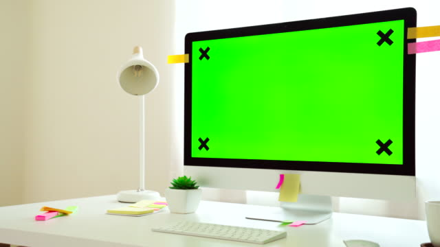 DOLLY shot : Green screen chroma key computer pc desktop on the desk at home office.
