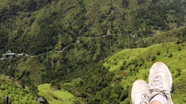 POV shot. Hiker sitting on the rock with a view POV shot. Hiker sitting on the rock with a view of Little Adam's peak in Ella, Sri-Lanka. colombo stock videos & royalty-free footage