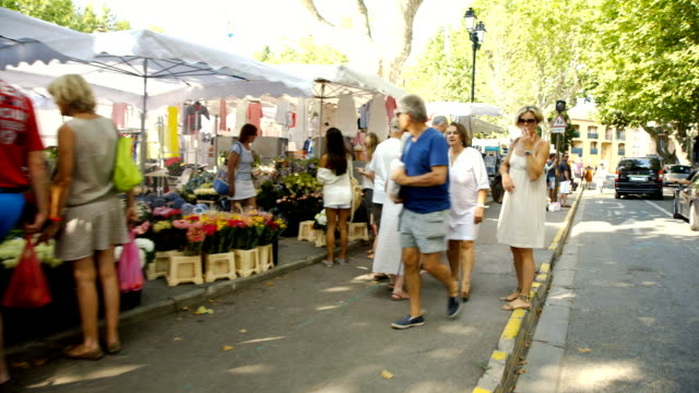 Shot moving down road alongside St-Tropez farmers market. video