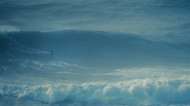 vídeos de stock e filmes b-roll de shot of a big wave surfer ride a massive wave in nazare, portugal. - portugal