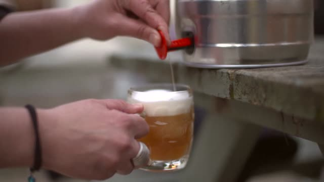 A shot of a lady pouring beer from a keg in a pub garden video