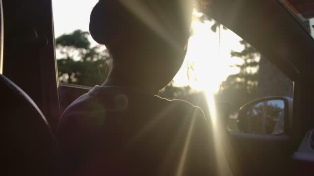 日没時に車の中でスマートフォンの写真を使用して長い髪のアジアの女性のSLO MOショット ビデオ