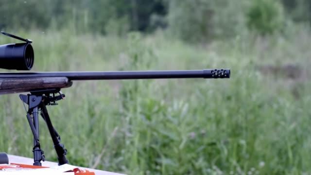 ein schuss eines scharfschützengewehrs von der tischansicht von der seite, auf einem hintergrund von bäumen. zusammenrücken. zeitlupe - schnauze stock-videos und b-roll-filmmaterial