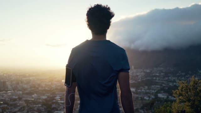 カメラで後ろ向きに面し、日の出に街と自然の景色を見下ろす若い白人男性のショット - スポーツウェア点の映像素材/bロール