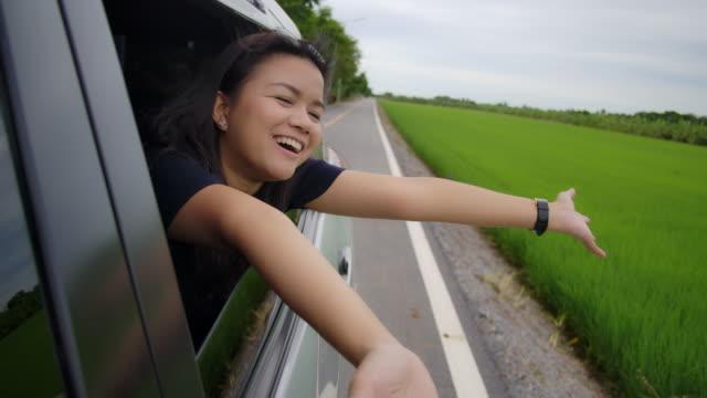 幸せな笑顔の腕で窓の外を見て車の中でロードトリップを楽しんでいるアジアの女性のSLOW MOショット ビデオ