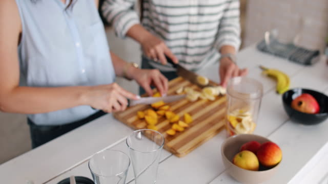 Shot of an attractive woman making a fruit smoothie in the kitchen. They prepare a healthy breakfast because they take care of their health. They chop a banana and a peach. Healthy diet, healthy food, weight loss video
